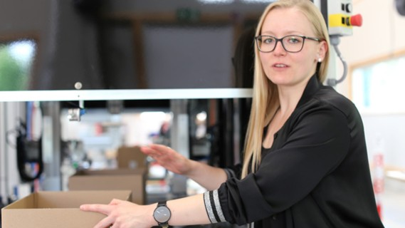 TGW Insights: Franziska places carton in carton height reducer.